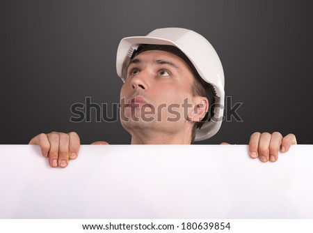Portrait of a workman in white hardhat holding a blank copy space and looking up