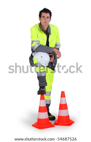Portrait of a workman with a safety helmet and traffic cones - stock photo