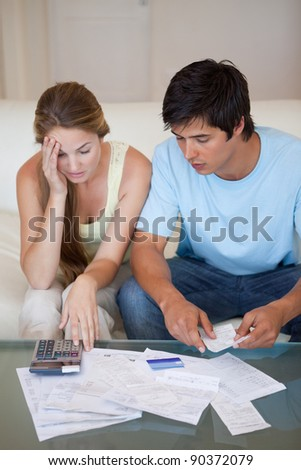 Portrait of a worried couple looking at their bills in their living room - stock photo