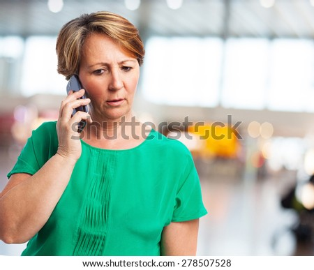 portrait of a worried mature woman talking on telephone - stock photo