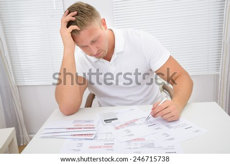 Portrait Of A Worried Young Man Calculating Unpaid Statements - stock photo