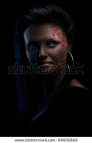 Portrait of a wounded young woman in low key