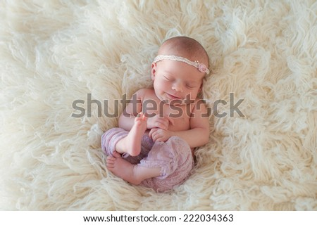 Portrait of a yawning ten day old newborn baby girl. She is curled up and sleeping on her back on a cream colored flokati rug.