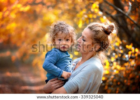 Portrait of a 1 year old boy enjoying outdoors with his mother in the woods.