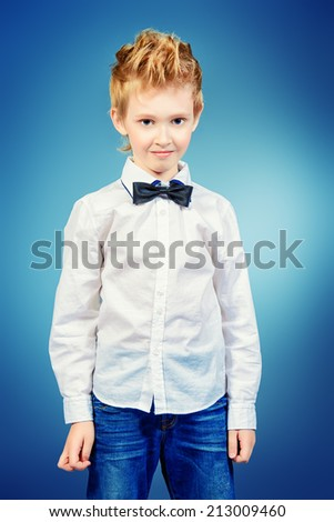 Portrait of a 7 year old boy wearing suit and bow-tie. Fashion shot. - stock photo
