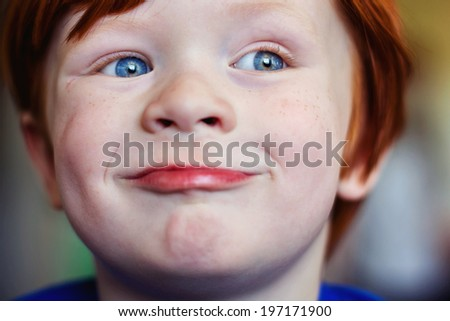 Portrait of a 4 year old redheaded boy -- image taken indoors using natural light  - stock photo