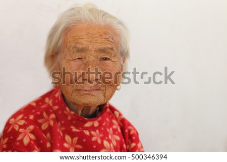Portrait of a 97 years old woman in white background, born in 1919, with depression, the last generation that bind the feet of woman