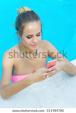 Portrait of a young adorable woman chatting on her cell phone in the swimming pool - stock photo