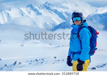 Portrait  of a young adult in a ski helmet and goggles, with high snowy mountains in the background - stock photo