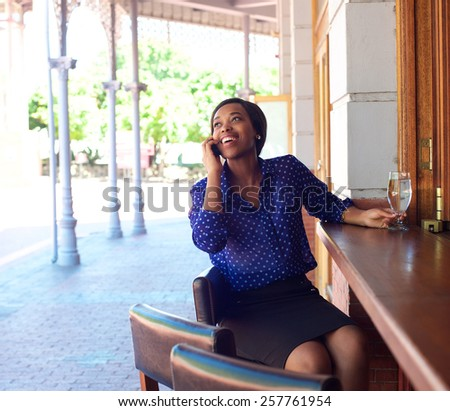 Portrait of a young african american business woman smiling with mobile phone at an outdoors bar - stock photo