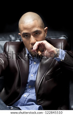 Portrait of a young African American businessman posing with a cigar - stock photo