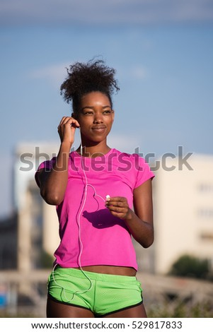 portrait of a young African American girl with headphones to run beautiful summer morning on city streets