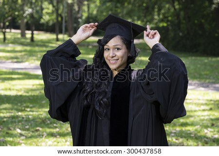 Portrait of a young african american graduate in a park/garden setting - stock photo