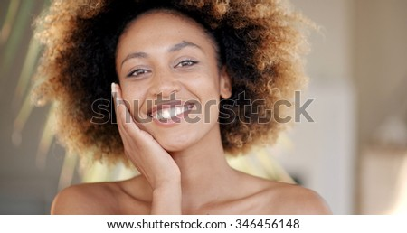 Portrait of a young african american woman against palm tree branch - stock photo