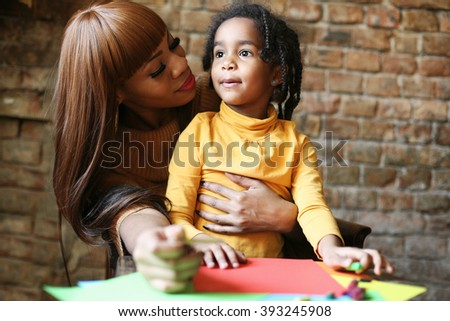 Portrait of a young African American woman and her daughter. drawing and communicate.  - stock photo