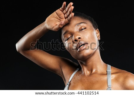 Portrait of a young african american woman relaxing after exercise workout isolated on the black background - stock photo