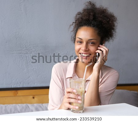 Portrait of a young african american woman smiling with mobile phone - stock photo