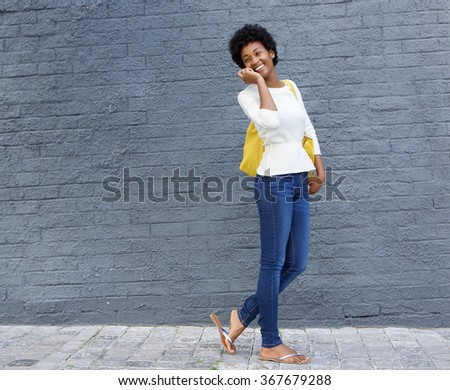 Portrait of a young african american woman walking and talking on cellphone - stock photo