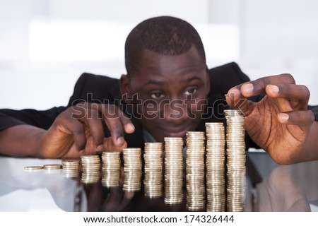 Portrait Of A Young African Businessman Stacking Coins In A Row On Desk - stock photo
