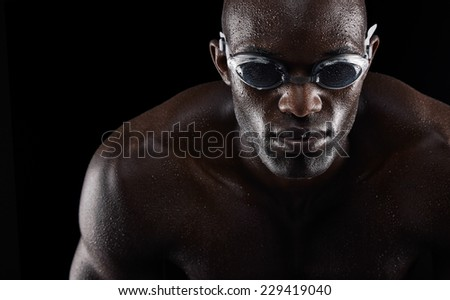 Portrait of a young african man wearing swimming goggles isolated on black background. Fit young athlete. - stock photo