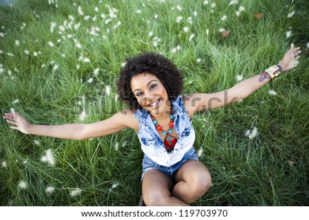 Portrait of a young african woman with raised arms in the park - stock photo