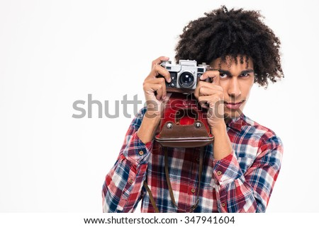 Portrait of a young afro american man making photo on retro camera isolated on a white background