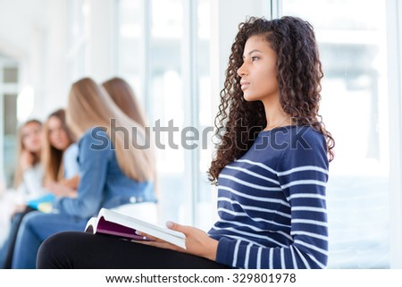 Portrait of a young afro american woman holding book and looking away in university hall - stock photo