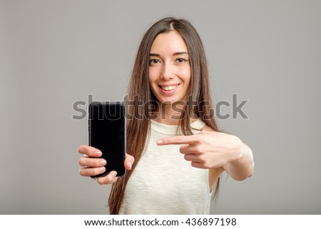 Portrait of a young amazed woman showing blank smartphone screen over gray background - stock photo