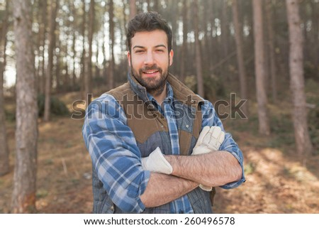 Portrait of a young and attractive bearded lumberjack posing in the forest with his arms crossed, smiling and looking at the camera. - stock photo
