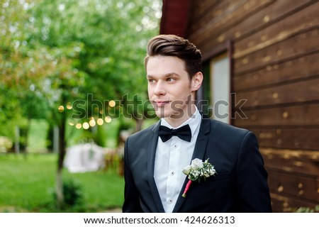 Portrait of a young and attractive groom at a wedding. Outdoor. He is smiling and happy