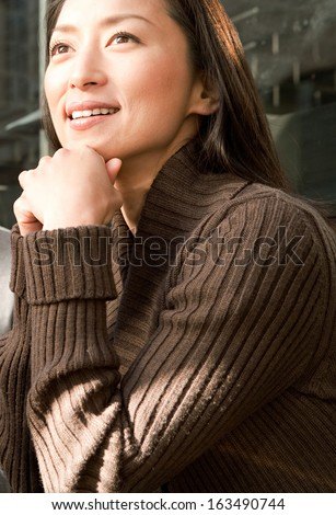 Portrait of a young and beautiful Japanese woman relaxing and leaning her chin on her hands, joyfully looking up while being an elegant and smart powerful woman, smiling outdoors. - stock photo