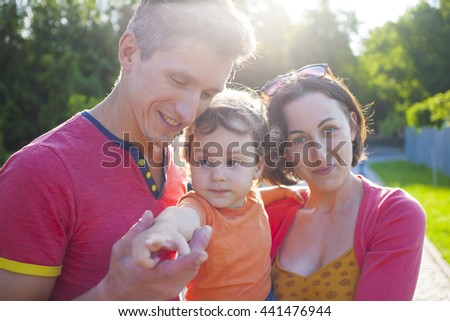 Portrait of a young and happy family with the baby on hands at mum. - stock photo