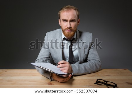 Portrait of a young angry businessman sitting at the table with clipboard over dark background - stock photo