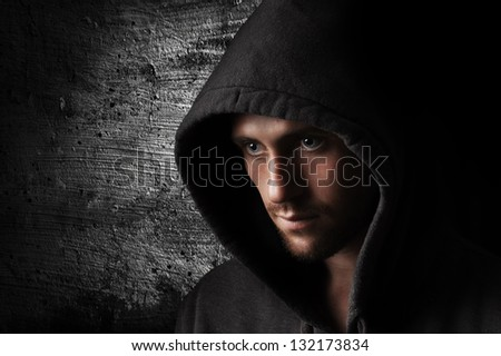 Portrait of a young angry man in the hood - stock photo