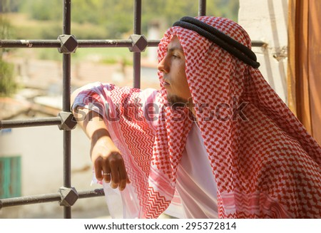 Portrait of a young arabic muslim man, who looking out the window - stock photo