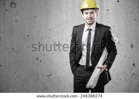Portrait of a young architect holding plans - stock photo