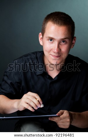 Portrait of a Young Artist at work on a drawing on a dark background