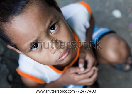 Portrait of a young Asian boy from poverty-stricken area. Natural light, Manila, Philippines. - stock photo