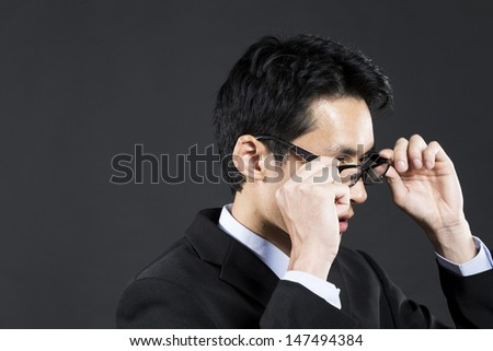 Portrait of a young Asian business man looking away. Dark grey background  - stock photo