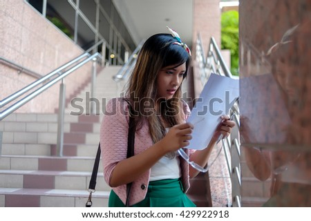 Portrait of a young Asian business woman reading a letter, walking at an outdoor office environment - stock photo
