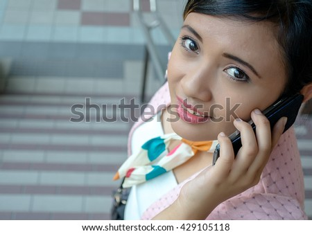 Portrait of a young Asian business woman smiling and talking on smart phone, walking at an outdoor office environment - stock photo