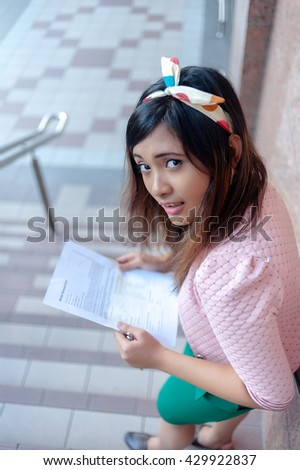 Portrait of a young Asian business woman smiling, reading a letter, walking at an outdoor office environment