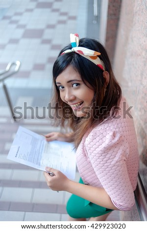 Portrait of a young Asian business woman smiling, reading letter, walking at an outdoor office environment - stock photo