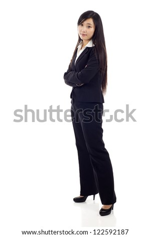 Portrait of a young Asian business woman standing with folded hands against white background