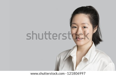 Portrait of a young Asian female doctor over gray background