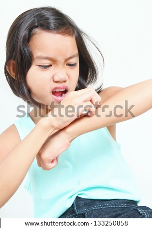 Portrait of a young asian girl scratching her arm. - stock photo