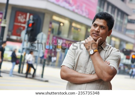 Portrait of a young asian indian businessman in city street - stock photo