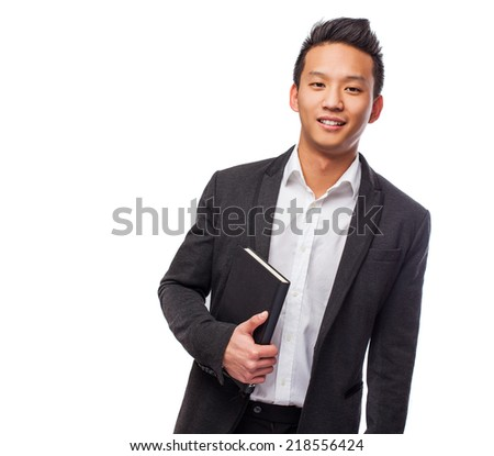 portrait of a young asian man holding a book - stock photo
