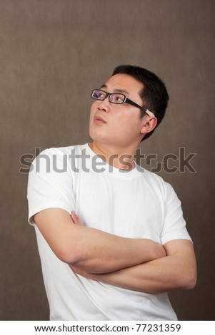 portrait of a young asian man in a white t-shirt with crossed arms looking up on grey background