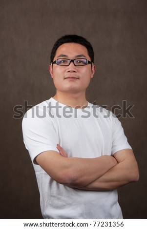 portrait of a young asian man in a white t-shirt with crossed arms on grey background